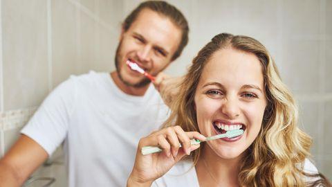 Zahngesundheit und Herz: Ein junges Paar putzt sich die Zähne