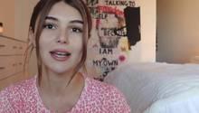 Eine junge Frau mit langen, braunen Haaren spricht in die Kamera. Sie hockt in einem Schlafzimmer und trägt ein rot-weißes Top.