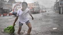 Ein Asiate in weißem T-Shirt und blaugemusterten Shorts zieht mit der rechten Hand einen Sack durch eine überflutete Straße