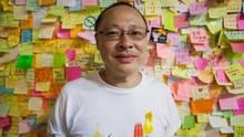 """Benny Tai posiert für das Foto vor de """"Democray Wall"""" (Demokratie-Wand) im Regierungsgebäudevon Hongkong"""