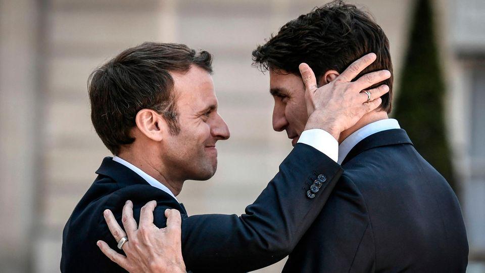 Emmanuel Macron (L) bids farewell to Canadian Prime Minister Justin Trudeau