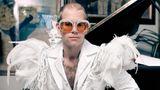 Elton John sitzt vor einem Flügel in weißem Anzug mit Federn auf den Schultern