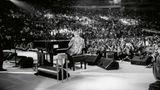 Elton John von sitzt mit dem Rücken zur Kamera vor Publikum am Flügel
