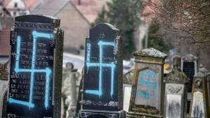 Mit Hakenkreuz beschmierte Grabsteine auf einem Friedhof