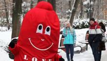 In einem roten Plüschkostüm geht jemand als Kondom verkleidet durch einen verschneiten Park