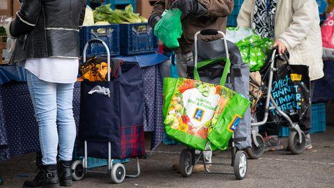 Gästeder Münchner Tafel stehen mit Plastiktüten an der Ausgabestelle