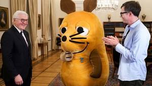 Bundespräsident Frank-Walter Steinmeier, die Maus samt Mausverdienstkreuz und Moderator Ralph Caspers
