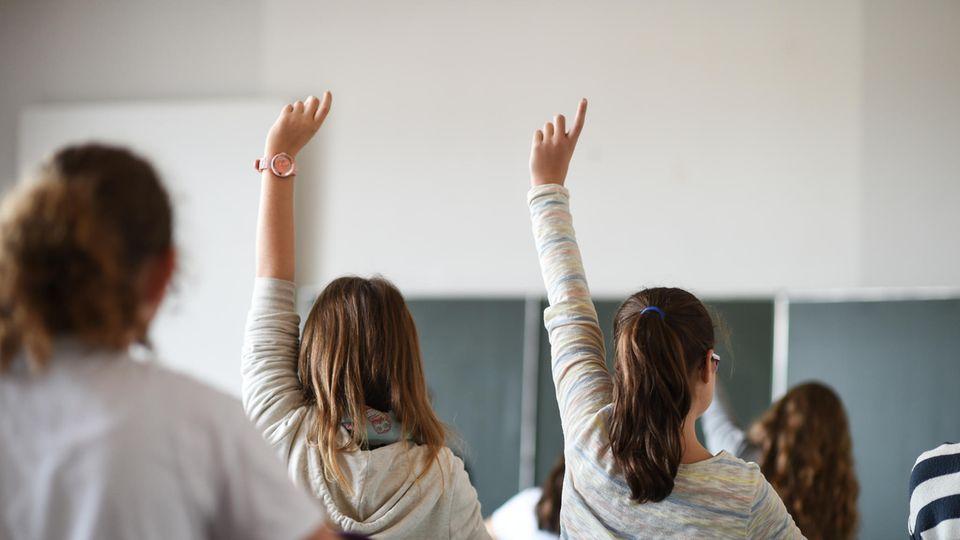 In einem Klassenzimmer sind Schülerinnen von hinten zu sehen. Zwei von ihnen melden sich. Im Hintergrund eine grüne Schultafel