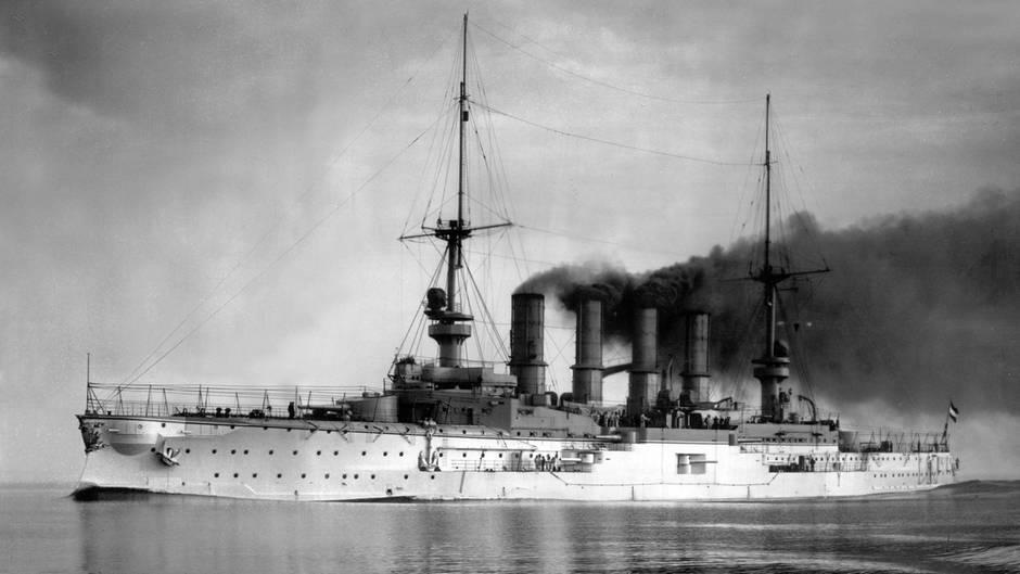 Ein schwarz-weiß-Foto zeigt ein Kriegsschiff mit vier stark rauchenden Schornsteinen