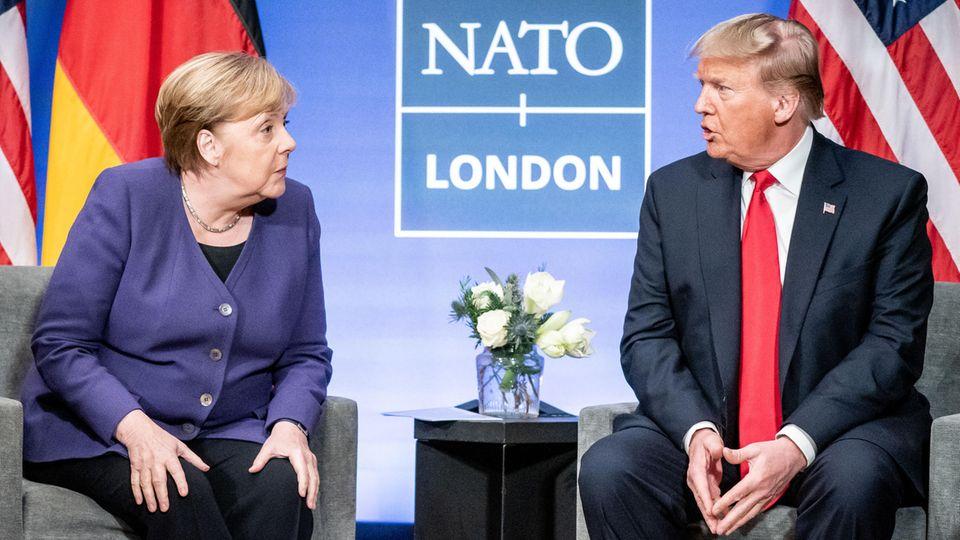 Angela Merkel blickt erstaunt auf Donald Trump