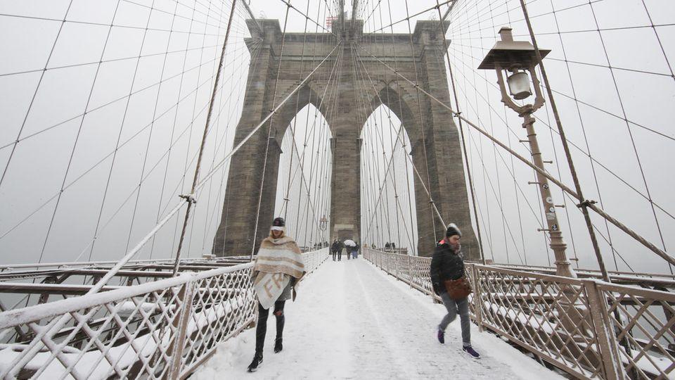 Zwei warm angezogene Menschen gehen im Schnee über die Brooklyn Bridge auf die Kamera zu