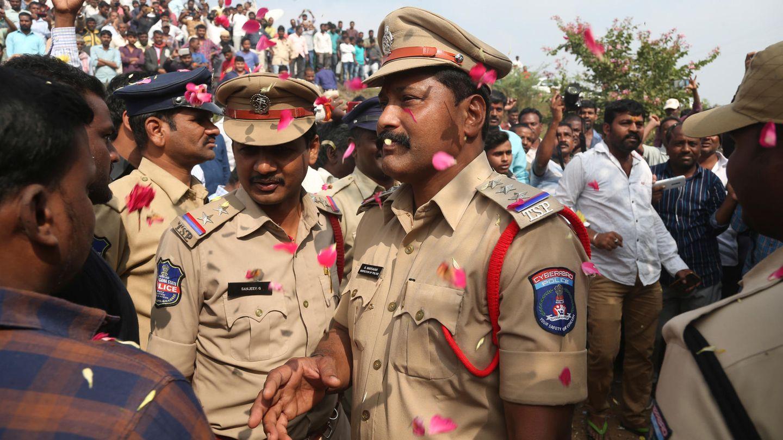 Menschen werfen Blütenblätter auf indische Polizisten