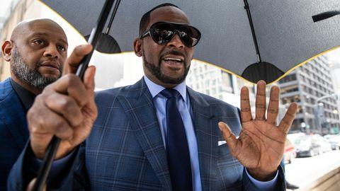 Sänger R. Kelly mit einem Regenschirm und Body Guard an seiner Seite
