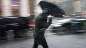 Wetter in Deutschland: Mann mit Regenschirm