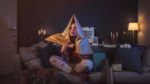 Frau sitzt auf dem Sofa und hat sich verzweifelt Geschenkpapier über den Kopf gezogen