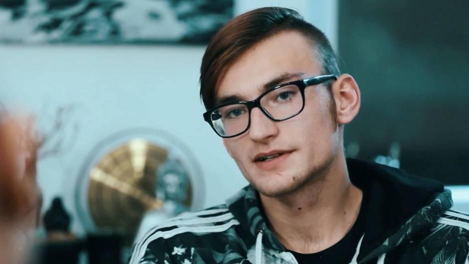 Ein junger Mann mit schwarzer Brille und Seitenscheitel legt den Kopf schräg, während er spricht