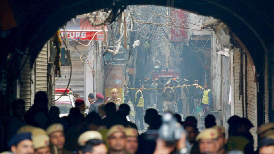 Ein Feuerwehrwagen steht in einer engen Gasse in einem abgesperrten Bereich vor einem Gebäude, in dem es gebrannt hat.