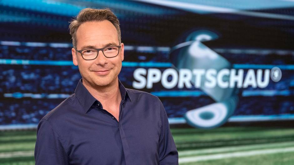"""Im dunkelblauen Hemd steht Moderator Matthias Opdenhövel im Fernsehstudio vor dem """"Sportschau""""-Schriftzug und lächelt"""