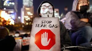 """Ein maskierter Demonstrant hält ein Schild mit der Aufschrift """"Stoppt Tränengas"""" während einer Kundgebung gegen den Einsatz von Tränengas durch die Polizei"""