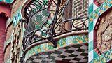 """Casa Vicens, 1878–1888, Calle de les Carolines, Barcelona. Prunkvoller kann man sich das Debut eines jungen Architekten kaum mehr vorstellen. Wie ein Märchenschloss aus """"Tausendundeiner Nacht"""" erhebt es sich vor dem Besucher der Calle de les Carolines 24 in Barcelona. Und doch ist es in Wirklichkeit ein recht kleines Haus, auch nicht die Heimat eines Prinzen, sondern das Wohnhaus eines Börsenmaklers.  Straßenseitiger Balkon im Anbau. Orange-gelbe Nelken füllen die farbigen Fliesen, so wie sie Gaudí auf dem noh leeren Grundstück gesehen haben soll."""