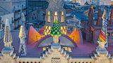 Palacio Güell, 1885_1889, Calle Nou de la Rambla, Barcelona. Wo man sich auch hinstellt in der Calle de la Rambla, es wird schwerfallen, den Palast, den Gaudí für seinen Freund Eusebi Güell erbaute, ganz in den Blick zu bekommen. Das liegt gewiss nicht an seiner Größe: Der Bauplatz ist nur 18 mal 22 Meter groß. Doch die Straße ist so eng, dass man nicht weit genug zurückweichen kann.  Die farbenfrohe Gestaltung der Dachaufsätze mit ihren Trencadís (Mosaike aus unterschiedlich großen Bruchstücken keramischer Fliesen, Marmor oder Glasscherben) macht das flache Dach zu einem stilisierten Wald inmitten der Enge der Altstadt. Um die zentrale Kuppel gruppieren sich Schornsteine und auch Belüftungen für die Ställe im Untergeschoss.
