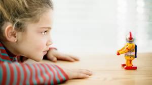 Ein Kind schaut auf einen Spielzeug-Roboter
