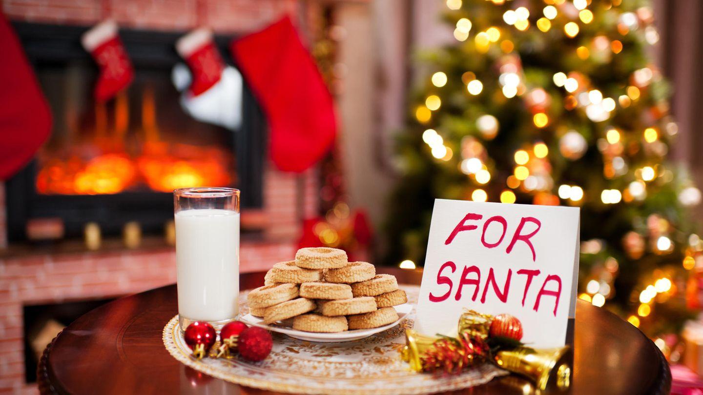 Milch und Kekse vor einem Weihnachtsbaum