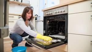 Backofen reinigen: Frau wischt mit einem Lappen ihren geöffneten Ofen ab