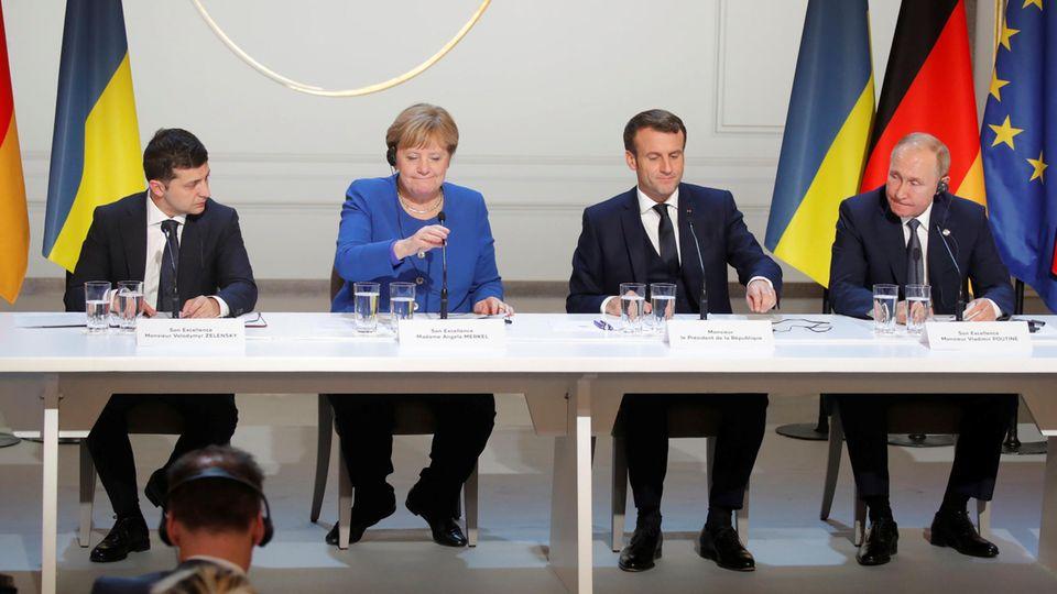 Selensky, Merkel, Macron und Putin sitzen in einer Reihe an Mikrofonen