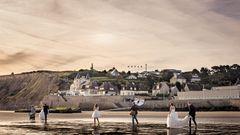 Ein Brautmoden-Fotoshooting morgens am Strand von Arromanches. Im Hintergrund sind Reste des Atlantikwalls zu sehen, mit denen die deutsche Wehrmacht eine Invasion der Alliierten zu verhindern suchte.