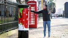 Eine Frau trägt einen Tannenbaum und wirft Post in einen roten Briefkasten