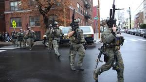 Polizisten gehen schwer bewaffnet über eine Straße
