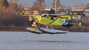 Ein gelbes Wasserflugzeug mit weißen Schwimmern fliegt knapp über der Wasseroberfläche eines Sees