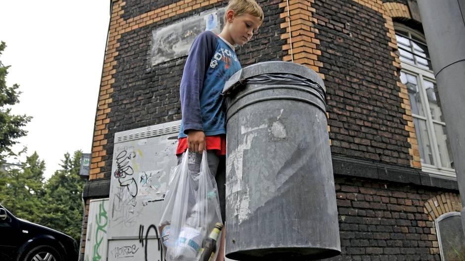 Ein Kind sammelt Pfandflaschen