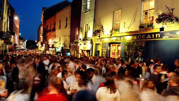 Menschen drängen sich durch die Haupteinkaufsstraße von Galway, die Shop Street. Neben Geschäften stehen hier viele Straßenmusiker und verbreiten auch bei schlechtem Wetter gute Laune.