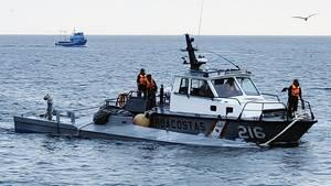 An einem Schiff der peruanischen Marine ist ein graues, flaches U-Boot festgemacht