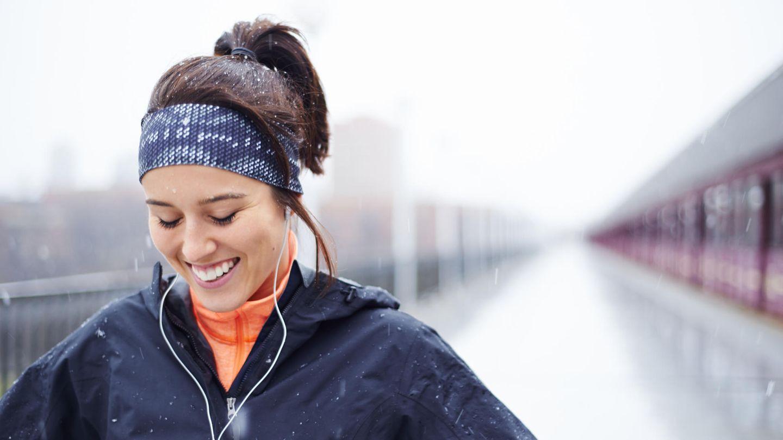 Eine junge Frau joggt im Schnee