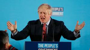 Boris Johnson steht mit ausgebreiteten Armen an einem Pult und hält eine Rede. Er trägt schwarzen Anzug und eine rote Krawatte