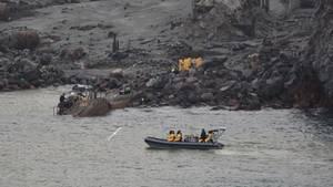 Vor der felsigen Küste von White Island treibt ein Schlauchboot mit drei gelb gekleideten Menschen darin