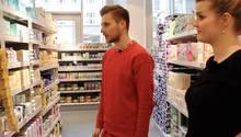 Ein junger Mann in rotem Sweathirt und eine junge Frau in schwarzem Top betrachten ein Supermarktregal voller Periodenprodukte