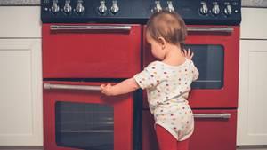 Ein Kleinkind steht am Backofen