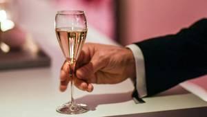 Eine Männerhand greift nach einem Champagnerglas, das auf einem weißen Tisch steht.