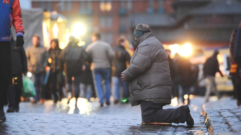 Ein Bettler kniet im Morgengrauen auf dem Fischmarkt am Hafen in Hamburg vor vorbeilaufenden Besuchern