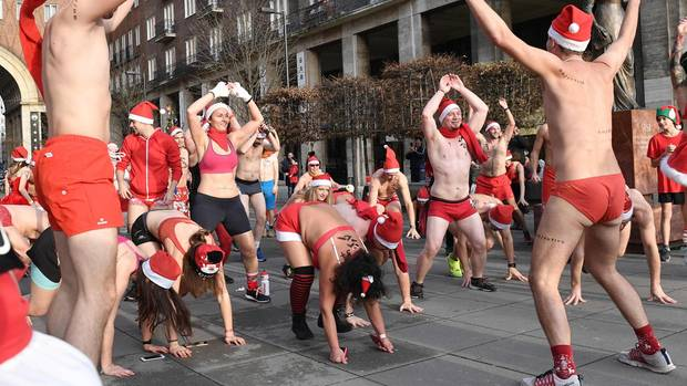 Budapest, Ungarn. Da heißt es kräftig aufwärmen: MitBadesachenund Weihnachtsmann-Mützen bekleidet bereiten sich diese Sportler aufeinenBenefizlaufim Zentrum der Stadt vor.