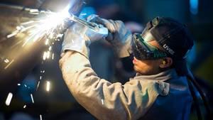 Ein Mann arbeitet in einer Firma an einem Stahlsegment