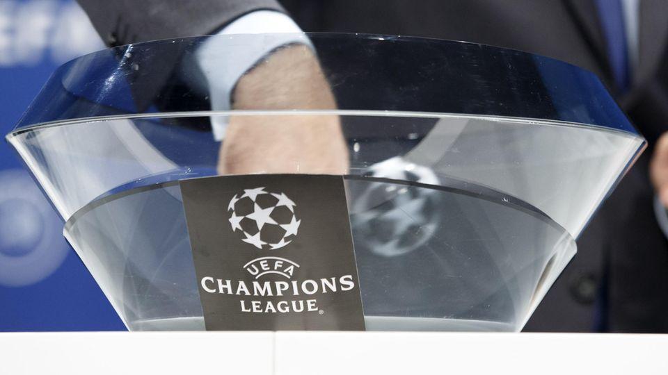 """Die Hand eines Mannes im Anzug steckt in einer Glasschale mit """"Champions League""""-Logo"""