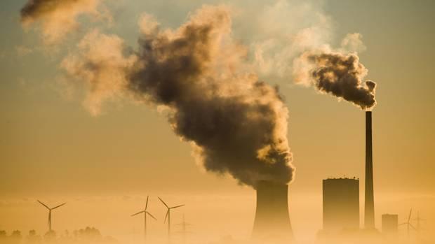 Aus dem Dunst ragen nebeneinander Silhouetten von Kraftwerks-Schornsteinen und Windrädern in den Himmel