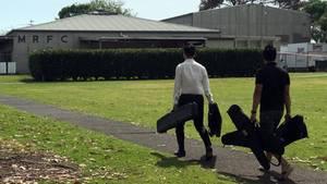 Zwei junge Männer gehen mit je zwei länglichen schwarzen Taschen über eine Wiese auf ein Gebäude zu