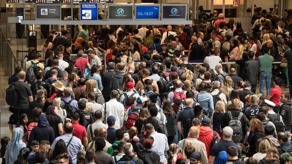 Im Stau vor der Security: Reisende stehen in einer langen Schlange vor der Sicherheitskontrolle im Terminal 2 des Flughafens