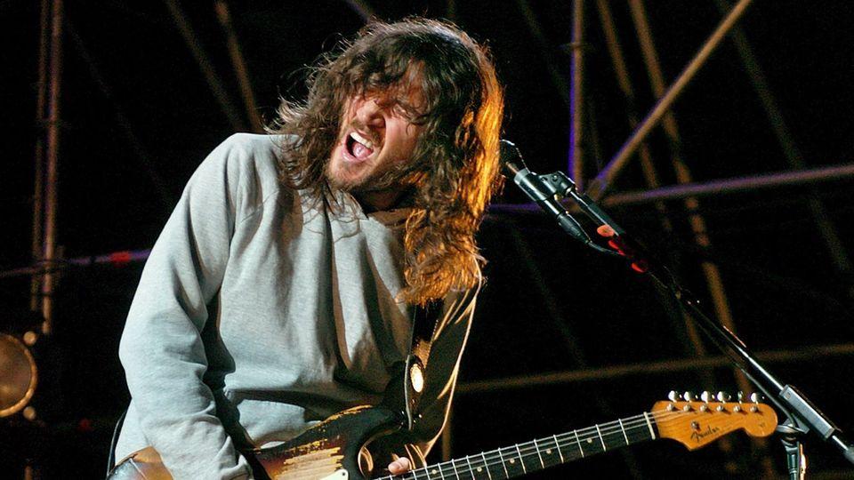 Ein Mann mit langen, braunen Haaren spielt mit offenem Mund und geschlossenen Augen E-Gitarre
